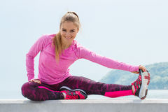 Slim girl in sporty clothes exercising by the sea, healthy active lifestyle. Slim girl wearing sporty clothes and exercising or stretching by the sea, healthy Stock Photos