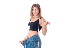 Slim girl stands on a large pants and holding  dumbbell in your hand isolated  white background Royalty Free Stock Images