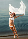 Slim girl in swimwear jumping with veil. On a beach stock image