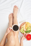 Slim girl tasting coffee while relaxing in bed. Flat lay of slim girl tasting fragrant black tea while relaxing and admiring delicious avocado Stock Images