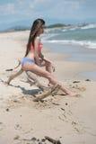 Slim girl wear bikini, sitting on dead tree's branch at the beach Stock Photos