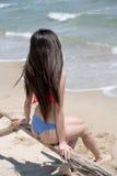 Slim girl wear bikini, sitting on dead tree's branch at the beach Stock Photo