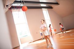Slim girl wearing white shorts trying to throw ball into basket