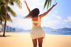 slim girl in white backside view poses with hands up on beach Stock Photo
