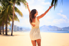 slim girl in white backside view poses with hands up on beach Stock Photos