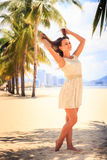 Slim girl in white frock barefoot poses against row of palms Royalty Free Stock Images
