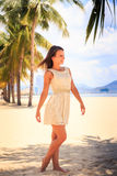 Slim girl in white frock barefoot poses against row of palms Stock Images