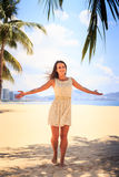 Slim girl in white frock poses with hands aside on beach Royalty Free Stock Photography