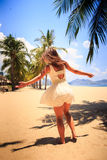 Slim girl in white frock poses with hands aside on beach Stock Photography