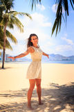 Slim girl in white frock poses with hands aside on beach Stock Image