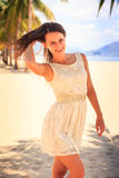 Slim girl in white frock smoothes hair against row of palms Royalty Free Stock Photo