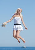 Slim girl in white is jumping Stock Image