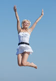 Slim girl in white is jumping Stock Images