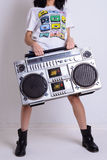 Slim girl in a white shirt and black shoes hold old tape cassette recorder Royalty Free Stock Images