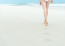 Slim girl in white swimsuit walking to ocean. Royalty Free Stock Photos