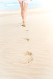 Slim girl in white swimsuit walking to ocean. Stock Photos