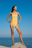 Slim girl in yellow pareo outdoors. Attractive young woman at the sea Royalty Free Stock Photography