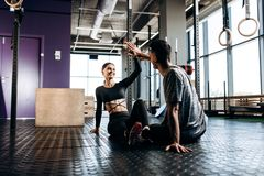 Slim girl and young man dressed in sports clothes are sitting on the floor and give five in the gym stock photos