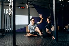 Slim girl and young man dressed in sports clothes are sitting on the floor and give five in the gym stock photography