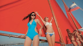 Slim girls in bikini dancing on a yacht. With red sails on sunset stock footage