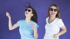 Slim girls dance happily. Two slim long-haired girls dancing happily, wearing light blue and white t-shirts, having great fun in the purple background, vacation stock video