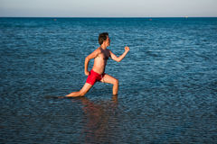 Slim guy posing in red swimwear in sea water Royalty Free Stock Photo