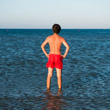 Slim guy posing in red swimwear in sea water Royalty Free Stock Image