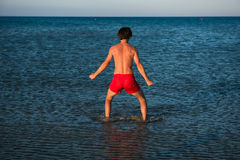 Slim guy posing in red swimwear in sea water Royalty Free Stock Images