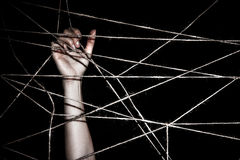 Slim hand behind the interlaced ropes Royalty Free Stock Photography