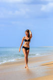 Slim happy girl walking in the beach shore Royalty Free Stock Images
