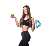 Slim and healthy young woman holding measure tape and apple isolated on white background. Weight loss and diet concept. Royalty Free Stock Image