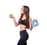 Slim and healthy young woman holding measure tape and apple isolated on white background. Weight loss and diet concept. Stock Images