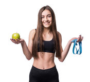 Slim and healthy young woman holding measure tape and apple isolated on white background. Weight loss and diet concept. Royalty Free Stock Images