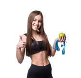 Slim and healthy young woman holding measure tape and apple isolated on white background. Weight loss and diet concept. Royalty Free Stock Photo