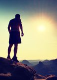 Slim hiker in pants on sharp cliff of rock empire is watching down to morning valley. Hot Sun above. Royalty Free Stock Images