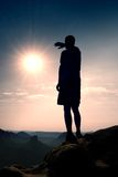 Slim hiker in pants on sharp cliff of rock empire is watching down to morning valley. Hot Sun above. Stock Photo