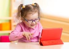 Slim jong geitje in bril die tabletpc met behulp van of eBook zitting bij lijst in haar ruimte stock fotografie