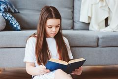 slim jong geitjemeisje die interessant boek lezen stock fotografie