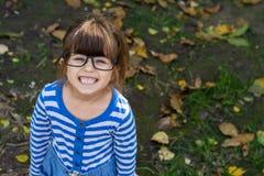 Slim kind met oogglazen die en camera glimlachen bekijken Jonge leerling klaar voor studie op school stock fotografie