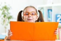Slim kindmeisje erachter van open boek Stock Afbeelding