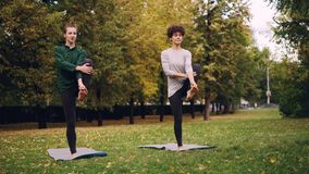 Slim ladies are exercising outdoors in park standing on one leg practising Padangusthasana during individual class with stock video footage
