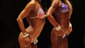 Slim ladies lined up in rear pose to show healthy muscular bodies at contest