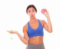 Slim lady choosing between sugar and fitness Stock Image