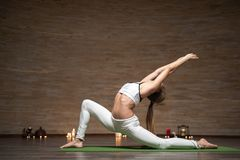 Slim lady doing low lunge pose while practicing yoga alone. Beautiful slim young lady spending time in yoga class and putting her hands up while practicing low stock photo