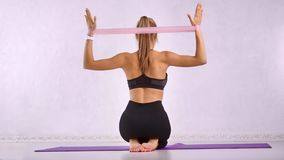 Slim lady fit coach making aerobics physical jerks for behind muscular body using stretch equipment