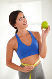 Slim lady holding apple and measuring tape Stock Photo