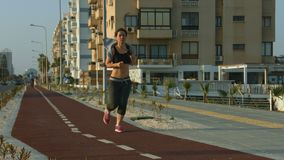 Slim lady jogging along urban road. Active lifestyle for wellness and health. Stock footage stock video