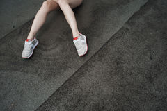 Slim lady legs against ruberoid or asphalt Royalty Free Stock Photography