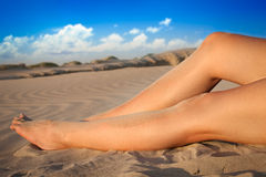 Slim legs on the beach. Young woman and slim legs on the beach Stock Photo