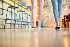 Slim legs. Two young women in leggins and high-heeled shoes walking along counter with bar chairs royalty free stock image